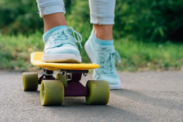 Pernas femininas de tênis em um skate em um close-up do parque