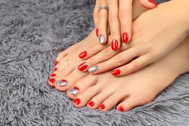 Pernas femininas e hans com unhas vermelhas no cobertor fofo. conceito de salão de beleza de manicure e pedicure.