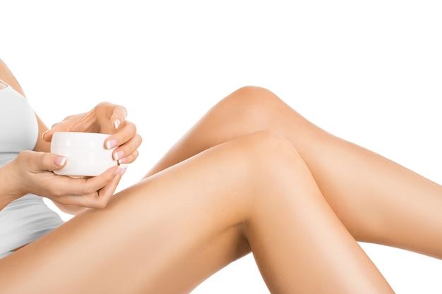 Pernas femininas e mãos com um pote de creme. isolado no branco