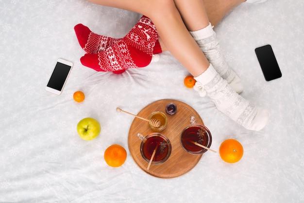 Pernas femininas e masculinas de casal em meias de lã quentes com laptop e smartphone. elementos de inverno