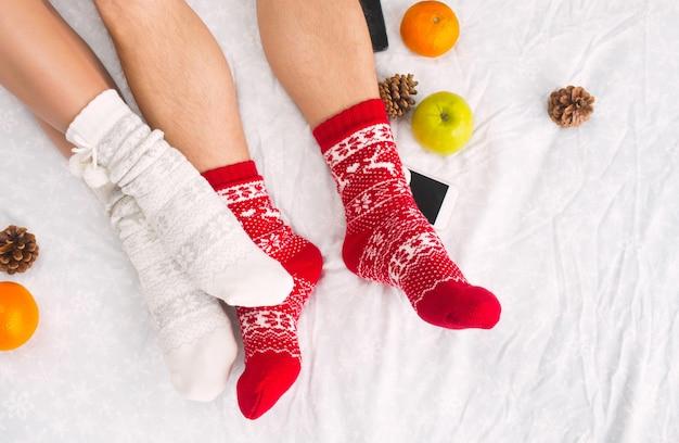 Pernas femininas e masculinas de casal em meias de lã quentes. elementos de inverno