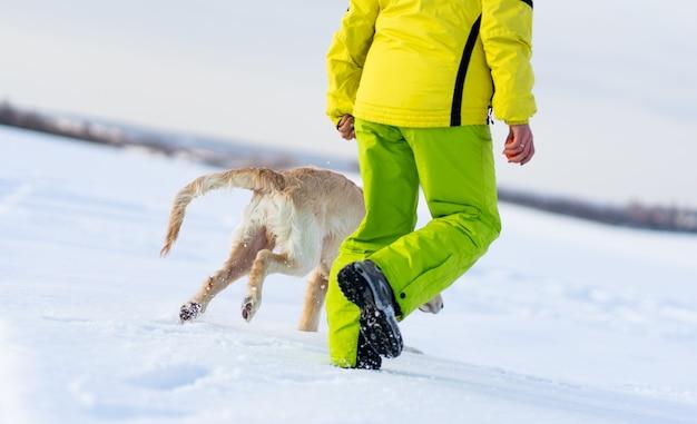 Pernas femininas e patas de cachorro correndo na neve cintilante