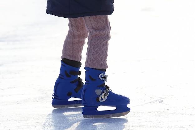 Pernas femininas em azul patinando na pista de gelo