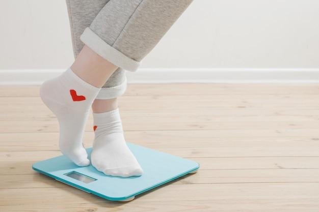 Pernas femininas em balanças eletrônicas em um piso de madeira