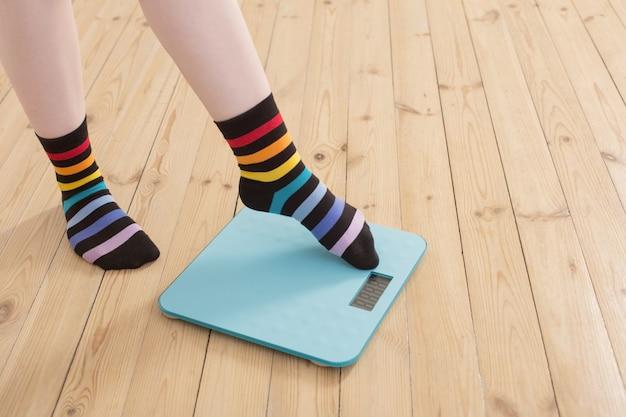 Pernas femininas em balanças eletrônicas no chão de madeira