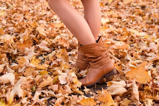 Pernas femininas em botas marrons. folhagem amarela sob os pés. conceito de outono