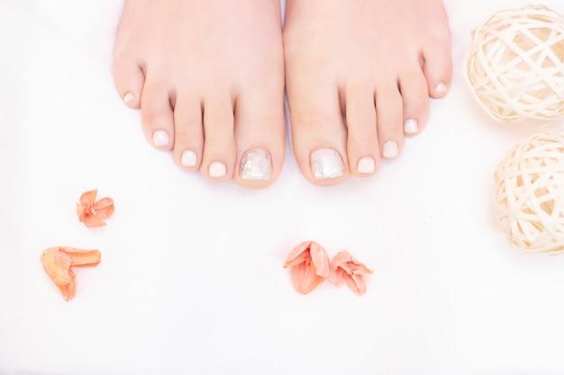 Pernas femininas em branco. as unhas ficam com um visual fresco e arrumado durante o procedimento de pedicure