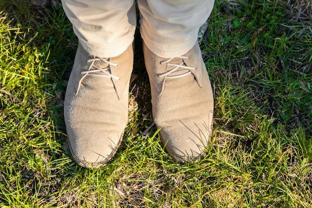 Pernas femininas em calças leves com sapatos bege na grama verde em um dia ensolarado