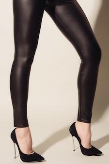 Pernas femininas em calças pretas justas de couro e sapatos de salto alto em cinza