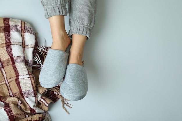 Pernas femininas em chinelos cinza em cinza