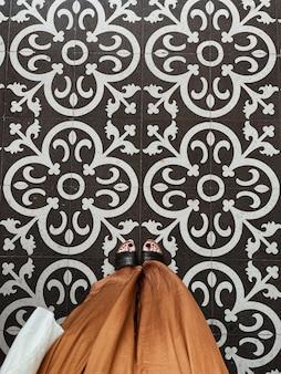 Pernas femininas em culotes marrons em ladrilho de mosaico ornamental