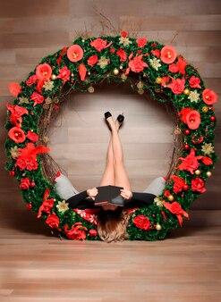 Pernas femininas em decorações de natal com um livro. menina lendo um livro no natal