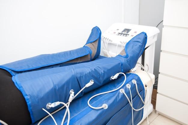 Pernas femininas em equipamento de pressoterapia anticelulite para emagrecimento em salão de spa