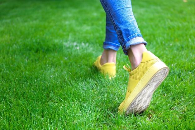 Pernas femininas em jeans e tênis amarelos na grama verde