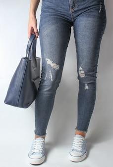 Pernas femininas em jeans e tênis, mulher segurando a bolsa de couro nas mãos em branco