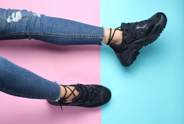 Pernas femininas em jeans justos e vestidos pretos da moda em uma mesa pastel. vista do topo.