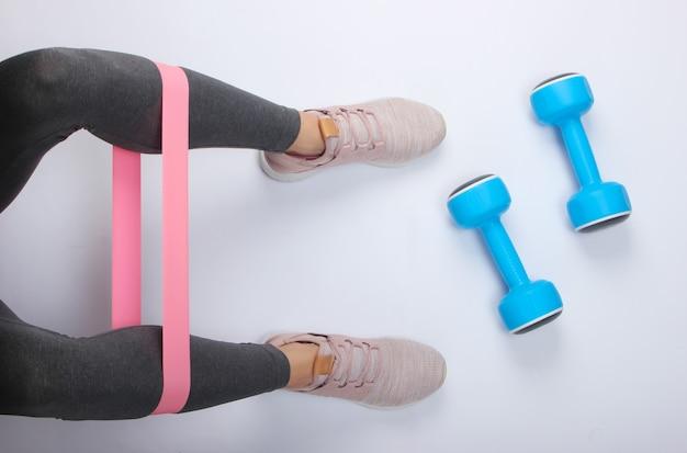 Pernas femininas em leggings esportivos e tênis, fazendo exercícios com elástico de fitness na superfície branca com halteres. vista do topo