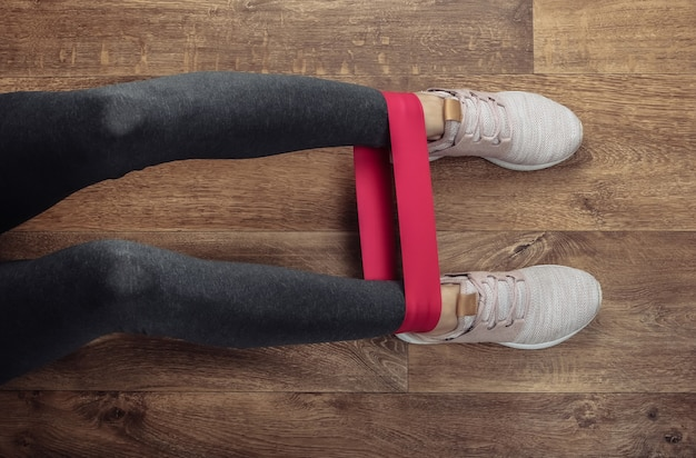 Pernas femininas em leggings esportivos e tênis, fazendo exercícios com elástico de fitness num piso de madeira. treino de fitness em casa. vista do topo