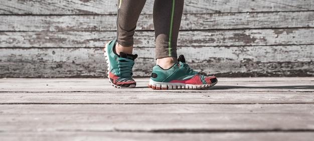 Pernas femininas em meia-calça e calçados esportivos com fundo de madeira, esportes conceituais