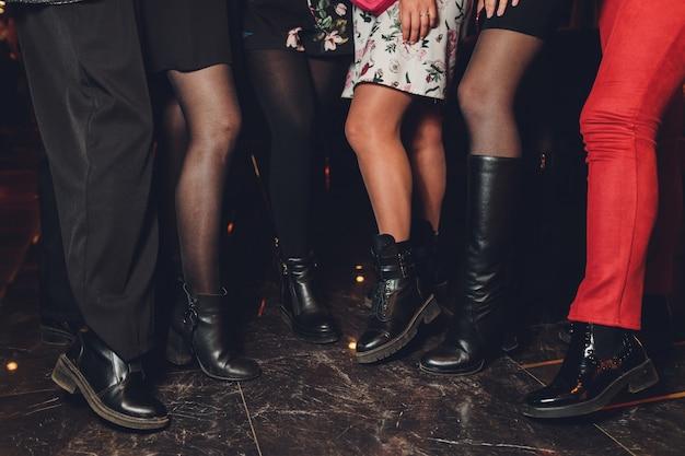 Pernas femininas em meia-calça preta em um restaurante.
