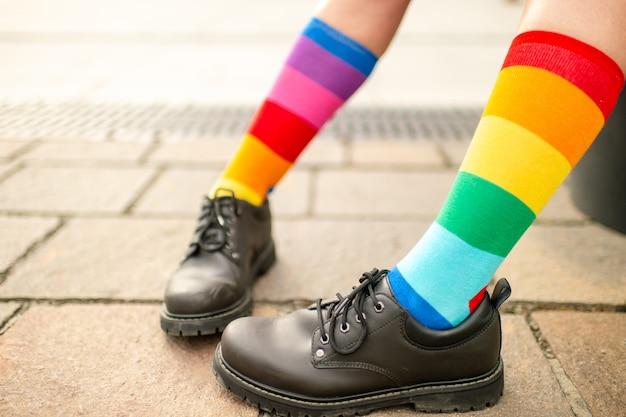 Pernas femininas em meias arco-íris lgbt usando botas masculinas