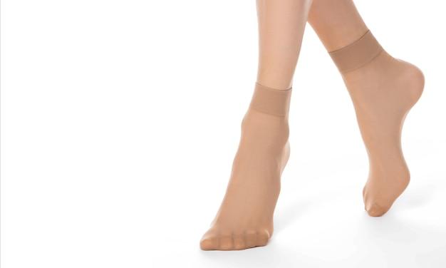 Pernas femininas em meias-calça em fundo branco