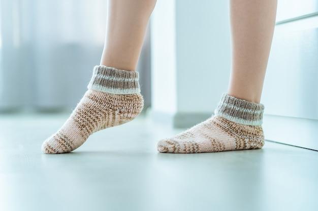 Pernas femininas em meias de inverno quentes de malha macias e aconchegantes em casa