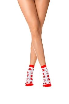 Pernas femininas em meias de natal em um fundo branco