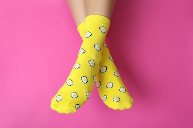 Pernas femininas em meias engraçadas rosa