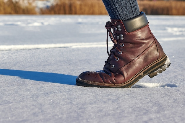 Pernas femininas em passos de botas impermeáveis de couro marrom na neve fresca. moda casual, calçados da moda.