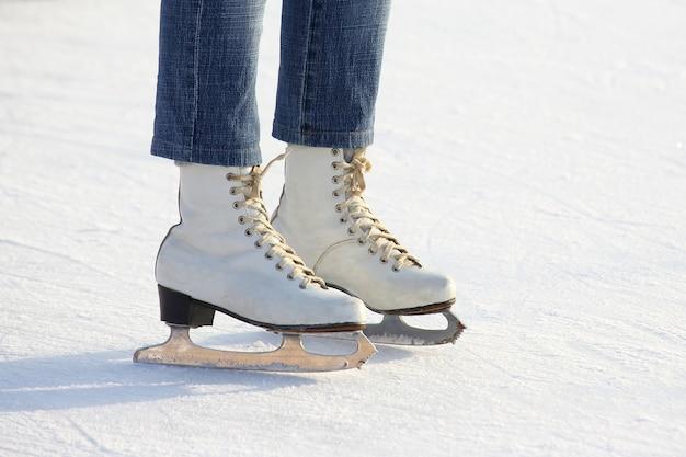 Pernas femininas em patins na pista de gelo
