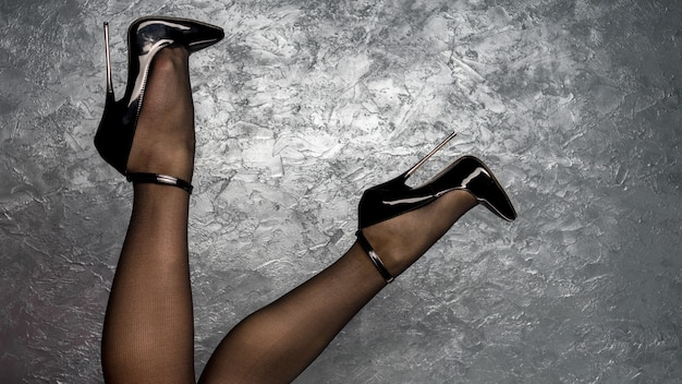 Pernas femininas em preto fetiche de couro envernizado brilhante, salto alto de estilete com tira no tornozelo perto da parede de estuque veneziano