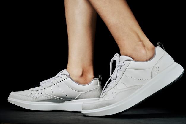 Pernas femininas em sapatos de desporto em um escuro. atleta de fitness pronto para exercício
