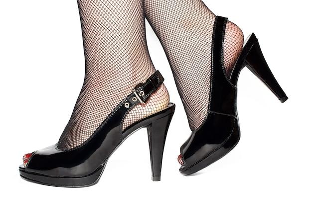 Pernas femininas em sapatos pretos isoladas