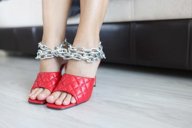 Pernas femininas em sapatos vermelhos amarrados com correntes cromadas cansadas após o conceito de dia de trabalho