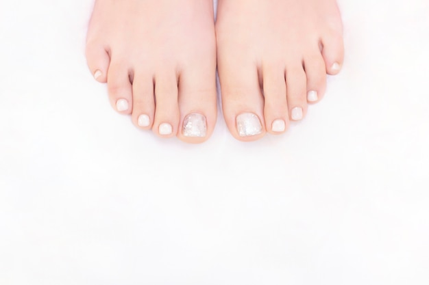 Pernas femininas em um fundo branco. as unhas ficam com um visual fresco e arrumado durante o procedimento de pedicure. feche de pernas femininas no salão spa.
