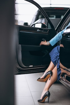 Pernas femininas fecham-se pelo automóvel