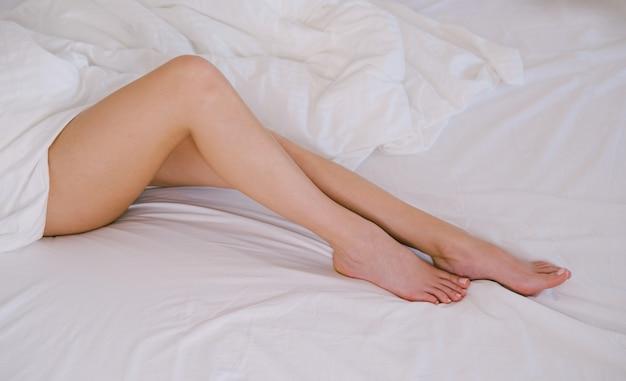 Pernas femininas fecham. tratamento spa para pés. pernas femininas em um fundo branco.