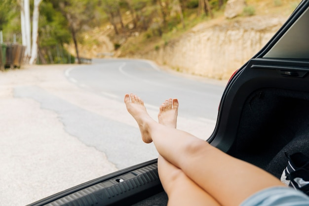 Pernas femininas fora do compartimento de bagagem de carro