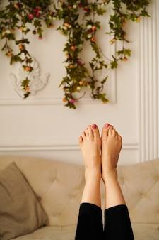 Pernas femininas levantadas na sala contra o fundo de um sofá bege - o conceito de liberdade de descanso ...