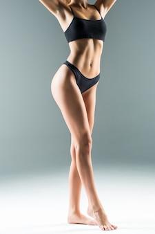 Pernas femininas magras e sexy, isoladas na parede cinza