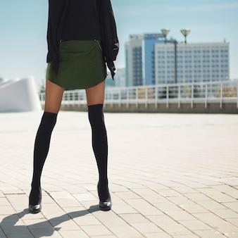 Pernas femininas muito finas em meias até o joelho em cima de meia-calça e saia curta de couro.