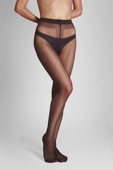 Pernas femininas muito finas em meias transparentes com um padrão clássico de bolinhas
