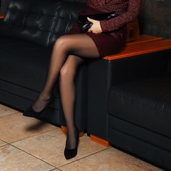 Pernas femininas na meia-calça no sofá de couro