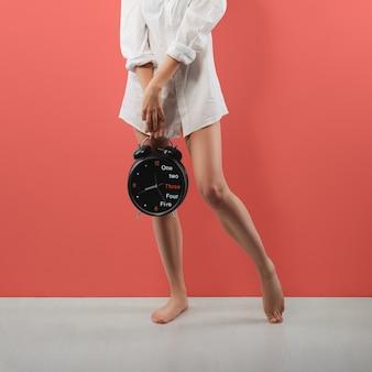 Pernas femininas nuas, camisa branca masculina e despertador enorme na mão