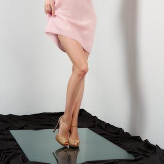 Pernas femininas nuas em sapatos de salto alto. levantando o vestido.