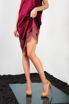 Pernas femininas nuas em sapatos de salto alto.