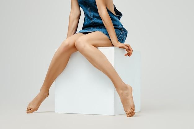 Pernas femininas nuas em um cubo de madeira branco