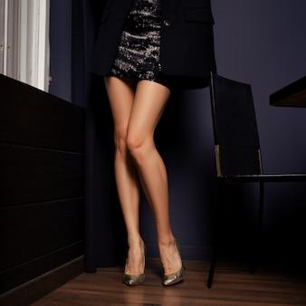 Pernas femininas nuas longas e finas em saia curta