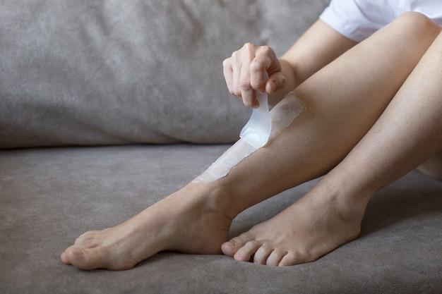 Pernas femininas peludas com creme de depilação, close-up. depilação das pernas em casa